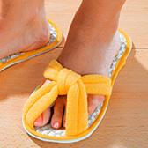 В желтых тапочках из флиса видны пальчики