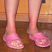 Загорелые ножки девушки в пляжных тапочках